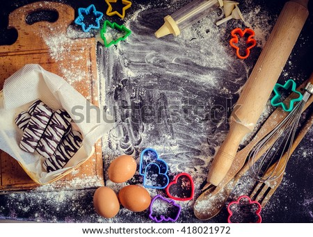 Baking children concept. Baking cookies for kids, top view of variety of baking utensils with different kind of flour, eggs and colorful cutters on black chalkboard. Family fun. Baby art. - stock photo