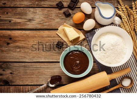 Baking chocolate cake in rural or rustic kitchen. Dough recipe ingredients (eggs, flour, milk, butter, sugar) on vintage wood table from above. Background layout with free text space. - stock photo