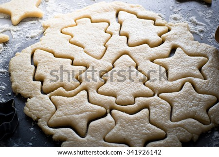 Baking Christmas cookies -  dough on the table, cookie cutters and cookies. - stock photo