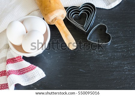 Baking concept for St. Valentines Day with heartshaped cutters and eggs on dark wooden table with copyspace