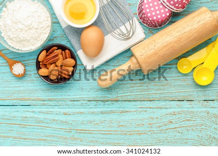 Baking cupcake with ingredients flour eggs almond nuts and rolling pin from above for background with space - stock photo