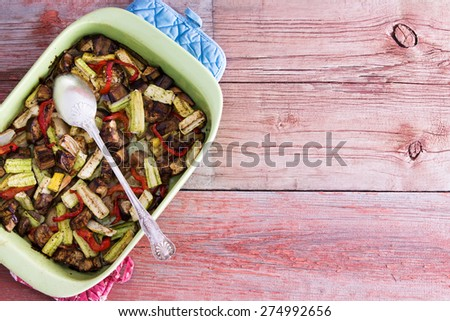 Baking dish filled with healthy roasted fresh vegetables for tasty vegetarian or vegan cuisine served on a rustic wooden table with copy space, overhead view - stock photo