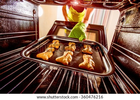 Baking Gingerbread man in the oven, view from the inside of the oven. Cooking in the oven. - stock photo