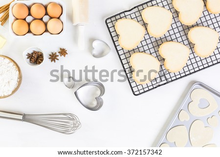 Baking heart shaped sugar cookies for Valentines Day. - stock photo