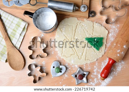 Baking holiday cookies still life shot form a high angle. Horizontal format with cookie dough, cutters, sifter, flour, rolling pin, cookie press, spoon, towel on butcher block surface. - stock photo