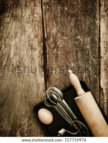 Baking in a rustic kitchen with an overhead view of an old manual egg beater and rolling pin lying on a baking tray with a fresh egg on an old wooden surface with copyspace - stock photo