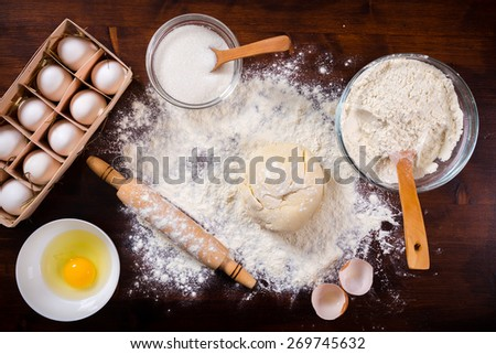 baking ingredients and dough on dark wooden table - stock photo