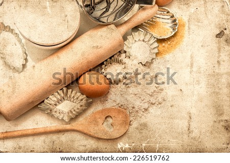 baking ingredients and tolls for dough preparation. flour, eggs, sugar, rolling pin and cookie cutters on white background. retro style picture - stock photo