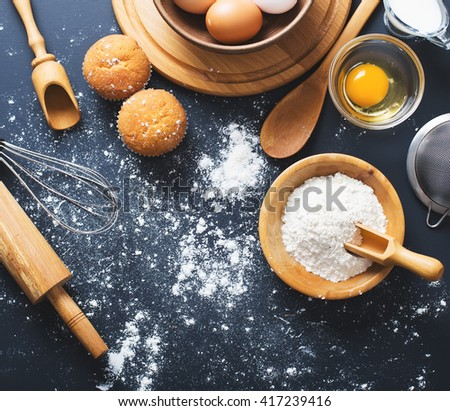 Baking ingredients. Bowl, eggs, flour, eggbeater, rolling pin and eggshells on black chalkboard from above. - stock photo