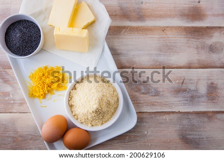 Baking ingredients for a lemon cake - eggs, butter, ground almonds, lemon zest and poppy seeds on a rustic wooden background with copy space.