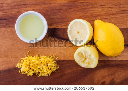 Baking ingredients for a lemon cake - lemon rind, squeezed lemon, lemon juice and lemon zester on a wooden background