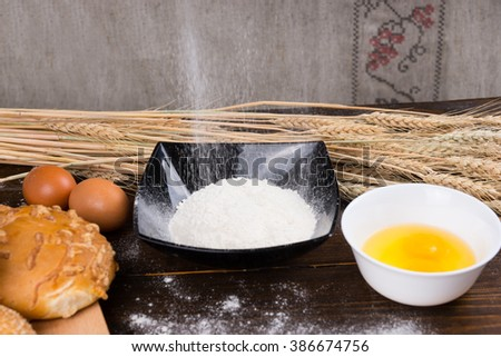 Baking ingredients for making bread with fresh broken eggs in a bowl with flour and a freshly baked cheese bun, copy space and ears of wheat behind - stock photo