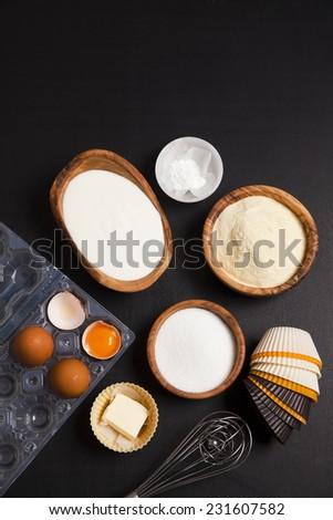 baking ingredients on dark. yogurt, semolina, eggs & butter. kitchen utensil. silicone muffins forms, wire whisk - stock photo
