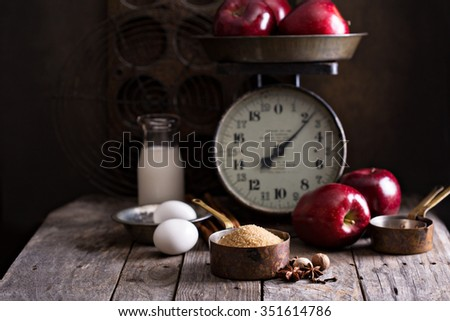 Baking ingredients on rustic table apples, eggs and sugar