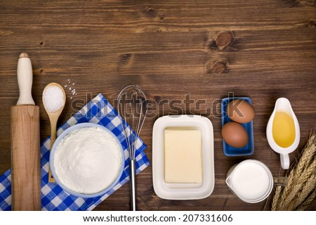 Baking ingredients on wooden background with text space - stock photo