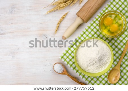 Baking ingredients, rolling pin and wheat ears on wooden table - stock photo