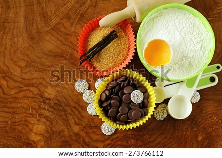 Baking ingredients (sugar, vanilla, flour, egg, chocolate) on a wooden table - stock photo