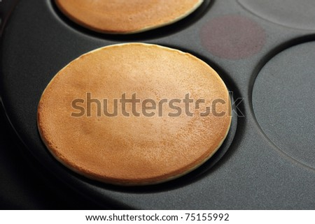 Baking pancakes on a crepe maker, a close up - stock photo