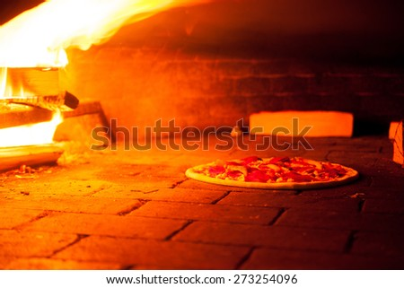 baking pizza in the oven with burning fire - stock photo