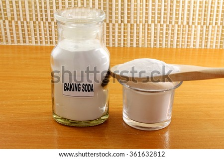 baking soda in bottle and wooden spoon - stock photo