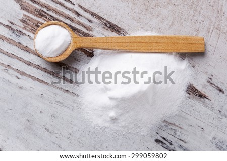 Baking soda on wooden spoon on white wooden textured background. - stock photo