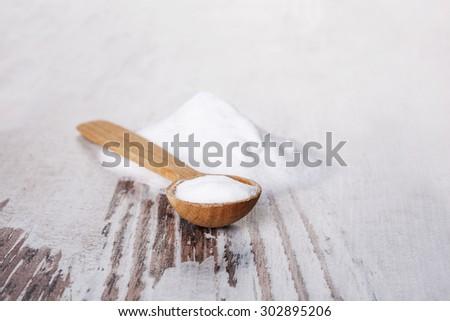 Baking soda on wooden spoon on white wooden textured background. - stock photo