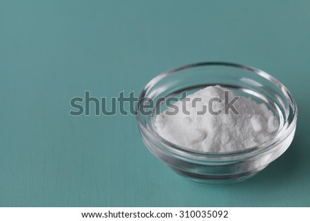 Baking soda, Sodium bicarbonate in glass bowl on wooden table - stock photo