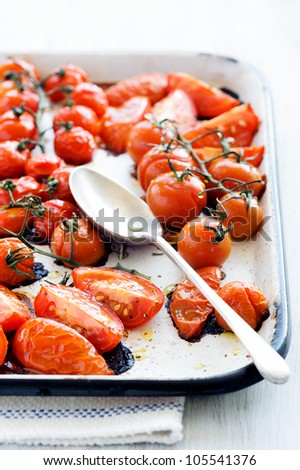 Baking tray filled with delicious juicy oven roasted tomatoes with large serving spoon, focus on front wedges of tomato - stock photo