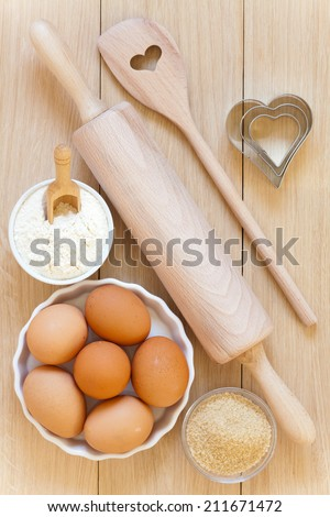 Baking utensils made �¢??�¢??of wood, eggs,flour and sugar in bowls on a wooden table