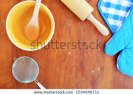 Baking utensils on old wooden board in flat lay with room for text