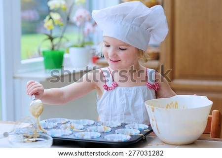 Baking with children. Little happy kid, adorable toddler girl in white chef hat filling cupcakes form with dough ingredients helping mother to prepare delicious pastry in the kitchen - stock photo
