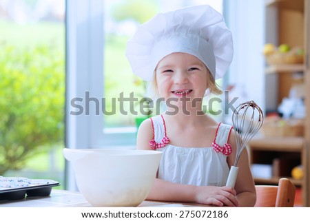 Baking with children: little happy kid, adorable toddler girl in white chef hat mixing dough ingredients in bowl helping mother to prepare delicious pastry in the kitchen - stock photo