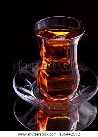 Bakinsky black tea in glass cup with ice cubes on dark background - stock photo