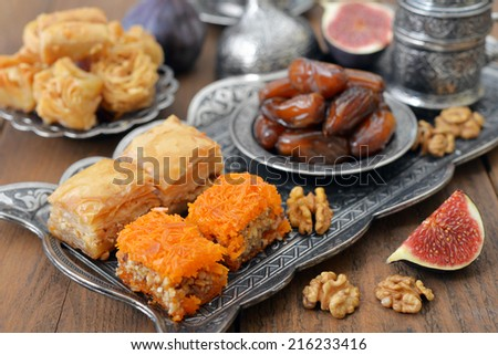 Baklava, figs, nuts and dry dates on tray. Small shallow DOF - stock photo