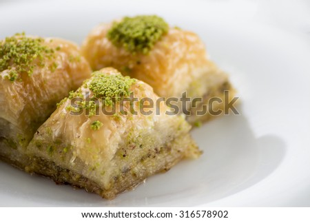 Baklava with pistachios and walnuts on white plate. Shallow depth of field - stock photo
