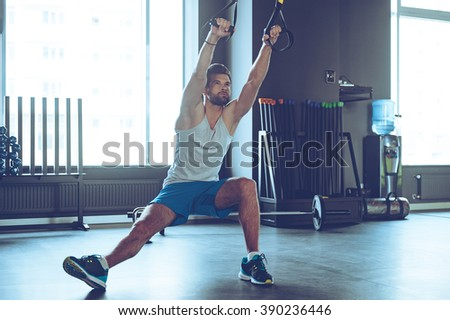 Balance and power. Full-length of young man in sportswear exercising at gym - stock photo
