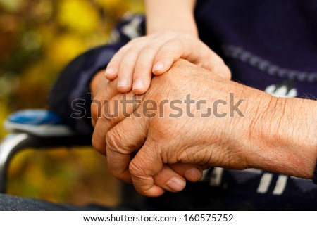 Balance concept - young hand holding the old one. - stock photo
