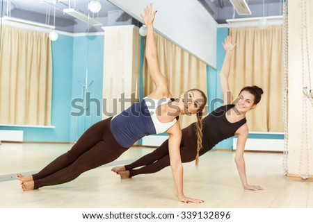 Balance. Full length shot of two beautiful young females doing side plank pose in yoga class - stock photo