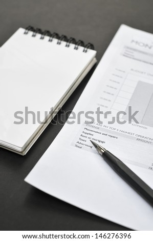 Balance sheet, blank notepad, and pencil on the table