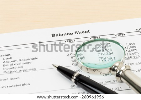 Balance sheet financial report with pen, and magnifier; document is mock-up