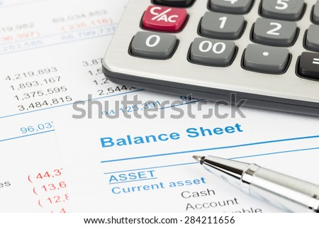 Balance sheet report with calculator and pen; document is mock-up