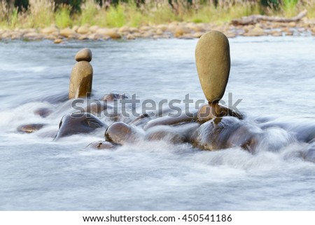 Balance stone in the middle of flowing river like zen garden. Soft and blurry image for background - stock photo
