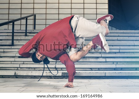 Balance stunt in an urban environment doing one hand stand - stock photo