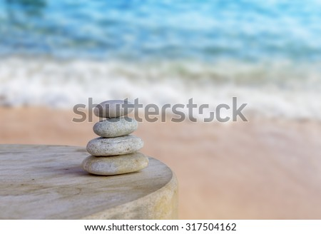 Balanced several Zen stones on blurred beautiful the beach background