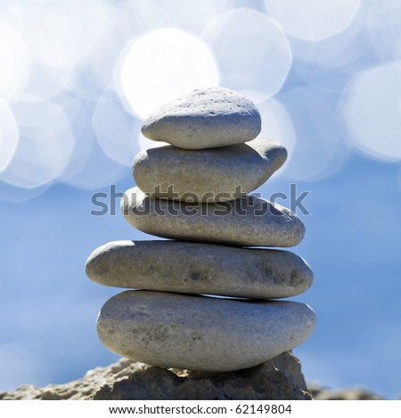 Balanced stack of pebbles over blue sea with reflections - stock photo
