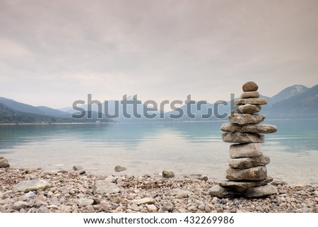 Balanced stone pyramide on shore of blue water of mountain lake. Blue mountains in water level mirror. Children built pyramid from pebbles - stock photo