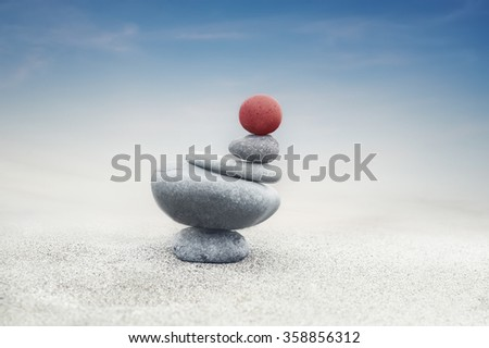 Balancing colorful zen stones pyramid on sandy beach under blue sky. Beautiful nature and spiritual consept - stock photo