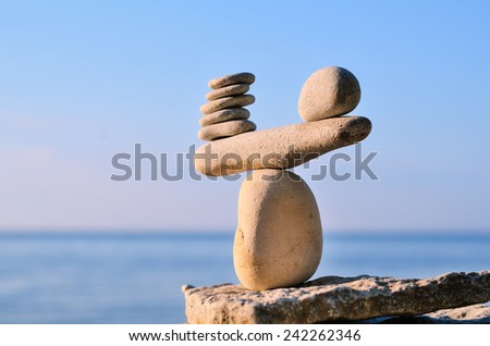 Balancing of white pebbles each other on the seacoast - stock photo