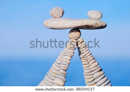 Balancing of white pebbles on the top of piles