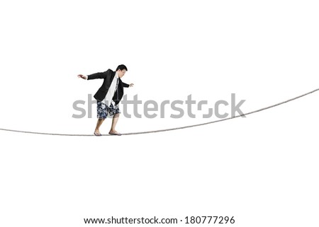 Balancing on rope isolated in white background - stock photo